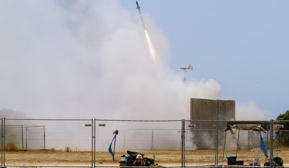 An Israeli soldier takes cover as an Iron Dome air defense system launches to intercept a rocket from the Gaza Strip, in Ashkelon, southern Israel, Tuesday, May 11, 2021. (AP Photo/Ariel Schalit) ** FILE **
