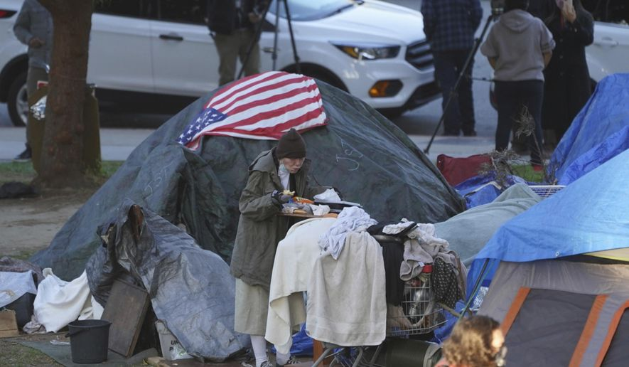 A woman eats at her tent at the Echo Park homeless encampment at Echo Park Lake in Los Angeles, March 24, 2021. California Gov. Gavin Newsom announced a $12 billion plan Tuesday, May 11, to confront the state's homelessness crisis. (AP Photo/Damian Dovarganes) ** FILE **