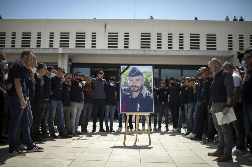 Police officers pay homage to a slain colleague at a police station in Avignon, southern France, Sunday, May 9, 2021. Police officers and civilians gathered to commemorate the death of a police officer who was killed Wednesday at a known drug-dealing site in the southern France city of Avignon. (AP Photo/Daniel Cole)