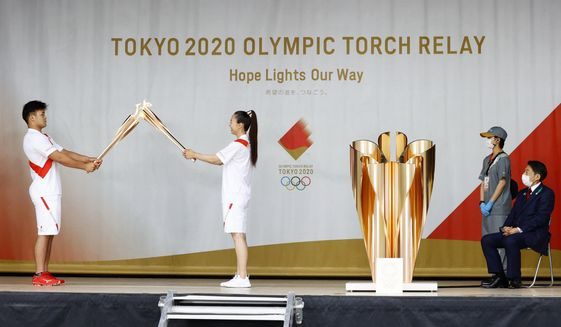 An ignition ceremony for the Tokyo Olympic torch relay is held at Heiwadai Athletic Stadium in Fukuoka, southwestern Japan, Tuesday, May 11, 2021. The torch relay was taken off public roads due to the coronavirus pandemic. The next week's torch relay is being pulled off the streets in Hiroshima prefecture, too, as COVID-19 cases rise in Japan. This is at least the sixth change to the relay - from rerouting to cancellation - in the last several weeks as cases surge in Japan. Organizers warned before the relay began that changes and delays were expected in the face of the pandemic. (Kyodo News via AP)