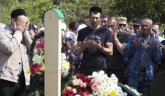 People pray next to the grave of Elvira Ignatieva, an English language teacher who was killed at a school shooting on Tuesday in Kazan, Russia, Wednesday, May 12, 2021. Russian officials say a gunman attacked a school in the city of Kazan and Russian officials say several people have been killed. Officials said the dead in Tuesday's shooting include students, a teacher and a school worker. Authorities also say over 20 others have been hospitalised with wounds. (AP Photo/Dmitri Lovetsky)