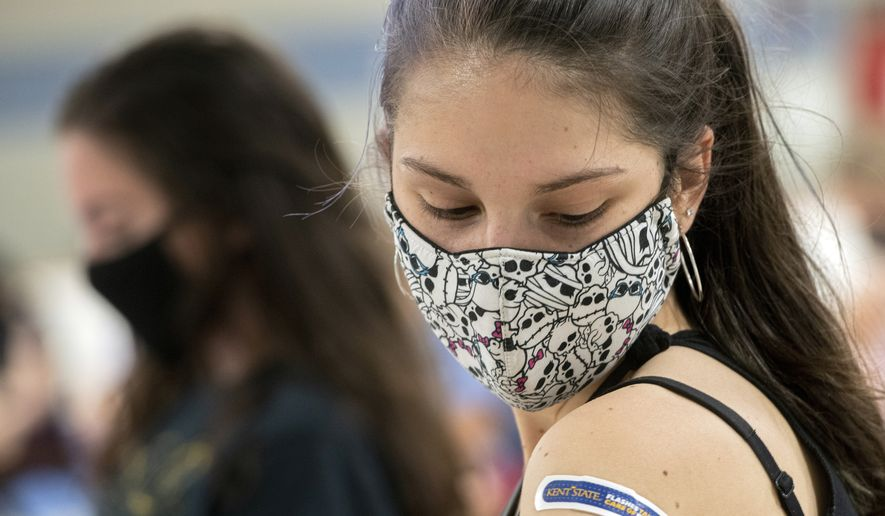 In this Thursday, April 8, 2021, file photo, Kent State University student Regan Raeth, of Hudson, Ohio, looks at her vaccination bandage as she waits for 15 minutes after her shot in Kent, Ohio. On Wednesday, May 12, 2021, Gov. Mike DeWine announced the end of the state's mask mandate as new COVID-19 cases decrease and more Ohioans get vaccinated. DeWine said the mask mandate will end June 2 except for nursing homes and assisted living facilities. (AP Photo/Phil Long, File)