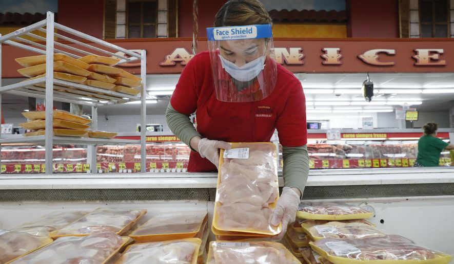 In this April 29, 2020, photo, a worker restocks chicken in the meat product section at a grocery store in Dallas. Rising prices for a variety of commodities are contributing to a jump in prices at the consumer level in 2021, with Americans paying more for meat, gasoline, items they keep in their homes and even the homes themselves. (AP Photo/LM Otero) **FILE**