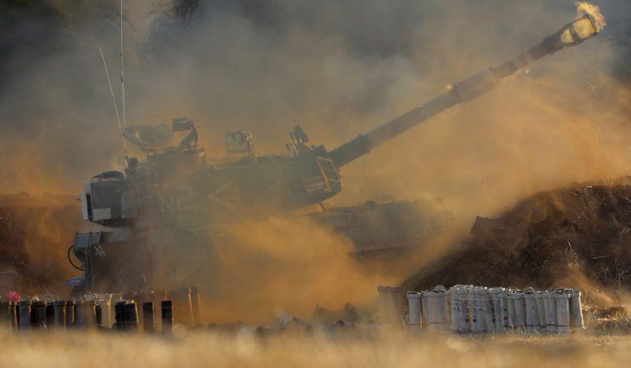 An Israeli artillery unit fires toward targets in Gaza Strip, at the Israeli Gaza border, Thursday, May 13, 2021. (AP Photo/Ariel Schalit)