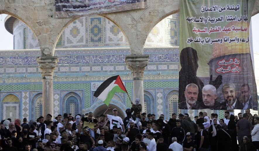A banner depicting Hamas leadership hangs on an archway as Muslims gather following Eid al-Fitr prayers at the Dome of the Rock Mosque in the Al-Aqsa Mosque compound in the Old City of Jerusalem, Thursday, May 13, 2021. Eid al-Fitr, festival of breaking of the fast, marks the end of the holy month of Ramadan. (AP Photo/Mahmoud Illean)