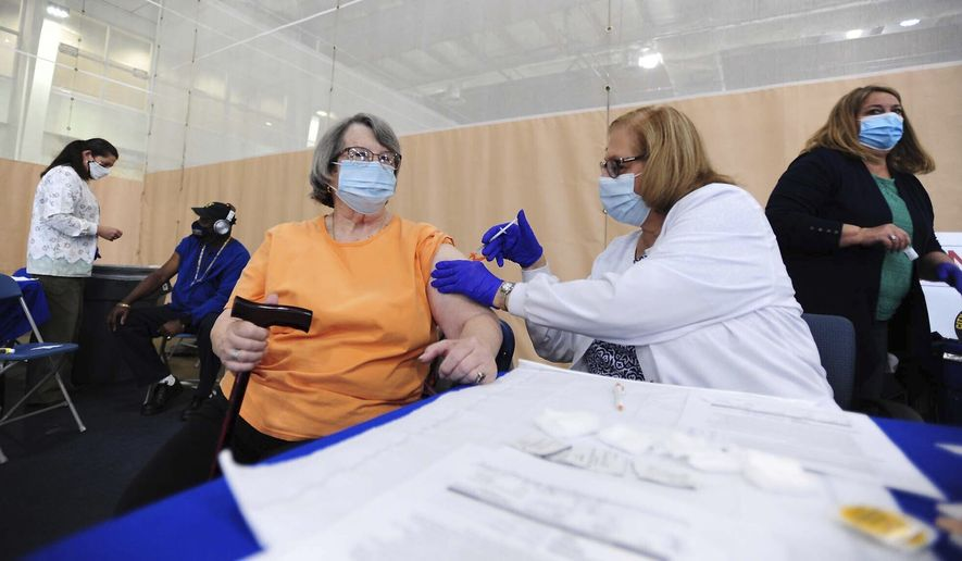Maryjo Morreale receives her second dose of the Moderna COVID-19 vaccine from Registered Nurse Eileen Attar, Thursday, May 13, 2021, at Wilkes University in Wilkes-Barre, Pa. The Wilkes-Barre Department of Health held the vaccine clinic. Approximately 480 people will be getting their second dose. (Mark Moran/The Citizens' Voice via AP)