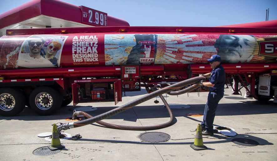 A fuel tanker driver delivers a 9,000-gallon load of fuel at the Sheetz in Raleigh, N.C., Thursday, May 13, 2021. Operators of the Colonial Pipeline say they began the process of moving fuel through the pipeline again on Wednesday, six days after the company shut it down because of a cyberattack. (Travis Long/The News & Observer via AP)