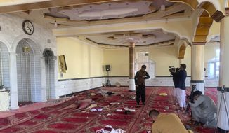 Afghan journalist take photos and film inside a mosque after a bomb explosion in Shakar Dara district of Kabul, Afghanistan, Friday, May 14, 2921. A bomb ripped through a mosque in northern Kabul during Friday prayers killing 12 worshippers, Afghan police said. (AP Photo/Rahmat Gul)