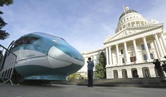 """FILE - In this Feb. 26, 2015 photo, a full-scale mock-up of a high-speed train is displayed at the Capitol in Sacramento, Calif. On Friday, May 14, 2021, Gov. Gavin Newsom proposed spending $11 billion on transportation improvements, half of it for a troubled bullet train intended to link California's major metropolitan areas eventually and projects supporting the 2028 Summer Olympics in Los Angeles. The Democratic governor billed the proposal as a way not just to repair decaying roads and bridges but to """"build a modernized transportation system for the next century."""" That also includes improving public transportation and the state's major ocean ports and encouraging more use of zero-emission vehicles. (AP Photo/Rich Pedroncelli, File)"""