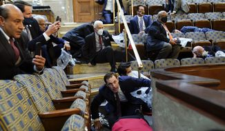 In this Jan. 6, 2021, file photo, people shelter in the House chamber as rioters try to break into the House Chamber at the U.S. Capitol in Washington. (AP Photo/Andrew Harnik, File)
