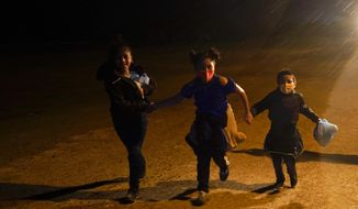 Three young migrants hold hands as they run in the rain at an intake area after turning themselves in upon crossing the U.S.-Mexico border Tuesday, May 11, 2021, in Roma, Texas. The number of unaccompanied children encountered on the U.S. border with Mexico in April eased from an all-time high a month earlier, while more adults were found coming without families, authorities said Tuesday. (AP Photo/Gregory Bull) **FILE**