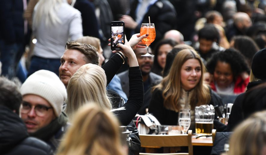 In this Monday, April 12, 2021, file photo, a woman takes a photo on her phone of her drink in Soho, London, as some of England's coronavirus lockdown restrictions were eased by the government. (AP Photo/Alberto Pezzali, File)