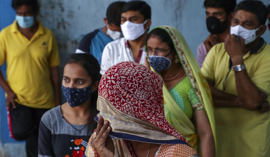 In this April 19, 2021, file photo, people wearing masks as a precaution against the coronavirus wait to test for COVID-19 at a hospital in Hyderabad, India. Misinformation about the coronavirus is surging in India as the death toll from COVID-19 rises. Fueled by anguish, distrust and political polarization, the claims are further compounding India's crisis. (AP Photo/Mahesh Kumar A, File)