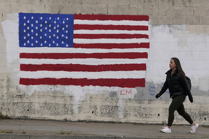 In this May 13, 2021, file photo, pedestrian walks in front of an American flag painted on a wall during the coronavirus outbreak in San Francisco. (AP Photo/Jeff Chiu, File)  **FILE**