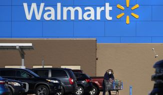 In this Nov. 18, 2020 file photo, a woman, wearing a protective face mask due to the COVID-19 virus outbreak, wheels a cart with her purchases out of a Walmart store, in Derry, N.H. Walmart, the world's largest retailer, said Friday, May 14, 2021 that it won't require vaccinated shoppers or workers to wear a mask in its U.S. stores, unless state or local laws say otherwise. Vaccinated shoppers can go maskless immediately, the company said. Vaccinated workers can stop wearing them on May 18. (AP Photo/Charles Krupa, File)