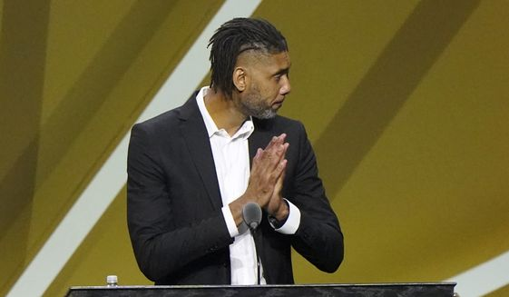 Tim Duncan dresses his hands together in praise for his presenter, David Robinson, to Duncan's left, while speaking as Duncan was enshrined into the 2020 Basketball Hall of Fame class, Saturday, May 15, 2021, in Uncasville, Conn. (AP Photo/Kathy Willens)