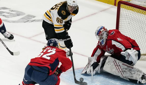 Boston Bruins right wing David Pastrnak (88) shoots but has his shot blocked by Washington Capitals goaltender Vitek Vanecek (41) during the first period of Game 1 of an NHL hockey Stanley Cup first-round playoff series Saturday, May 15, 2021, in Washington. (AP Photo/Alex Brandon)