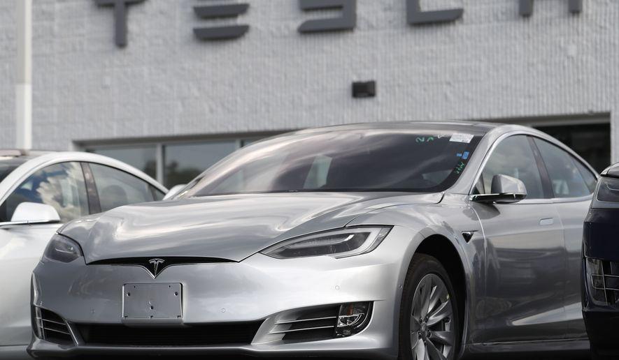 This July 8, 2018, file photo shows a Tesla 2018 Model 3 sedans sitting on display outside a Tesla showroom in Littleton, Colo. (AP Photo/David Zalubowsi, File)