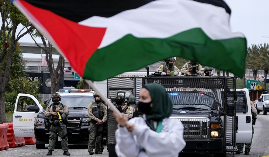 A demonstrator waves the flag of Palestine as police officers guard outside the Federal Building during a protest against Israel and in support of Palestinians, Saturday, May 15, 2021, in the Westwood section of Los Angeles. (AP Photo/Ringo H.W. Chiu)