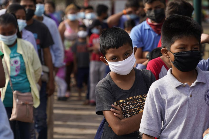 Children and adults wait in lines for donated food at a makeshift camp for migrants near the U.S.-Mexico border Friday, May 14, 2021, in Reynosa, Mexico. Growing numbers of migrant families are making the heart-wrenching decision to separate from their children and send them into the U.S. alone. (AP Photo/Gregory Bull) ** FILE **