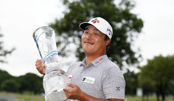 K.H. Lee, of South Korea, holds the Champions Trophy after winning the AT&T Byron Nelson golf tournament in McKinney, Texas, Sunday, May 16, 2021. (AP Photo/Ray Carlin)