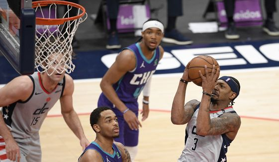 Washington Wizards guard Bradley Beal (3) goes to the basket against Charlotte Hornets forward P.J. Washington, center, during the first half of an NBA basketball game, Sunday, May 16, 2021, in Washington. (AP Photo/Nick Wass)