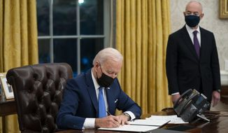 In this Tuesday, Feb. 2, 2021, file photo, Secretary of Homeland Security Alejandro Mayorkas looks on as President Joe Biden signs an executive order on immigration, in the Oval Office of the White House in Washington. (AP Photo/Evan Vucci, File)