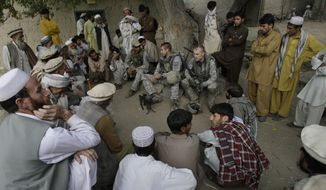 In this Nov. 3, 2009, file photo, Lt. Thomas Goodman, center, of the 2nd Battalion, 12th Infantry Regiment, 4th Brigade Combat Team, 4th Infantry Division meets with villagers in Qatar Kala in the Pech Valley of Afghanistan's Kunar province with his interpreter Ayazudin Hilal, center left with hat. Hilil served as an interpreter alongside U.S. soldiers on hundreds of patrols and dozens of firefights in eastern Afghanistan, earning a glowing letter of recommendation from an American platoon commander and a medal of commendation. Still, Hilal was turned down when he applied for one of the scarce special visas that would allow him to relocate to the U.S with his family. (AP Photo/David Guttenfelder, File)