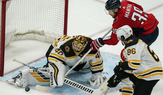 Washington Capitals right wing Anthony Mantha (39) cannot get the puck past Boston Bruins goaltender Tuukka Rask (40) with Bruins defenseman Kevan Miller (86) nearby during the third period of Game 2 of an NHL hockey Stanley Cup first-round playoff series Monday, May 17, 2021, in Washington. (AP Photo/Alex Brandon)