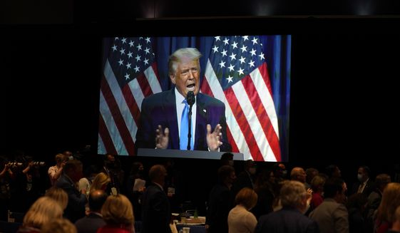 In this Monday, Aug. 24, 2020, file photo, a screen displays then-President Donald Trump as he speaks on stage during the first day of the Republican National Committee convention in Charlotte, N.C. (AP Photo/Evan Vucci) ** FILE **