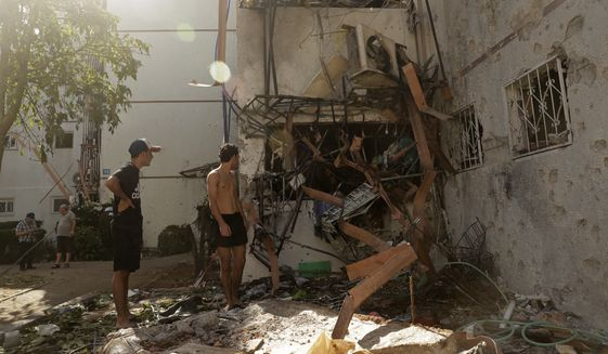 People look at a residential building after it was hit by a rocket fired from the Gaza Strip, in Ashdod, southern Israel, Monday, May 17, 2021. (AP Photo/Maya Alleruzzo)