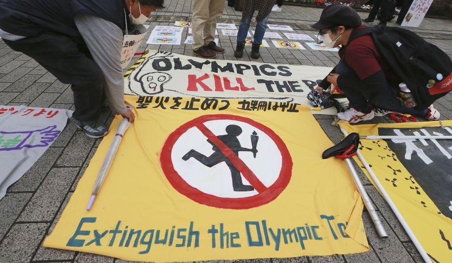 Demonstrators unfold signs to protest the Tokyo 2020 Olympics in Tokyo, Monday, May 17, 2021. (AP Photo/Koji Sasahara)