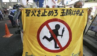 """People carry a banner reading """"Extinguish the Olympic torch"""" during a march, calling for the cancellation of the 2020 Tokyo Olympics to be held in the middle of a pandemic, in Tokyo, Monday, May 17, 2021. (AP Photo/Koji Sasahara)"""