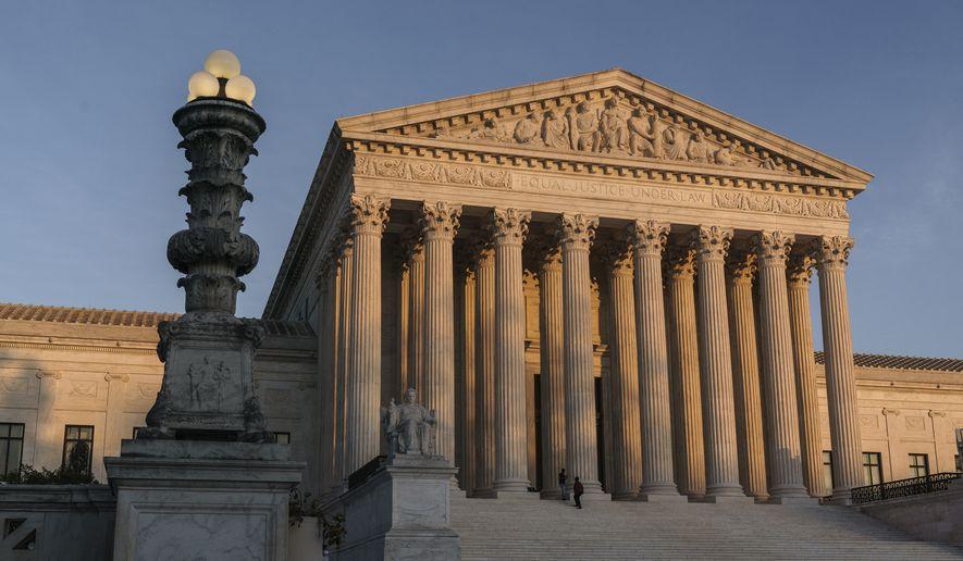 In this Nov. 6, 2020, photo, the Supreme Court is seen at sundown in Washington. (AP Photo/J. Scott Applewhite) ** FILE **