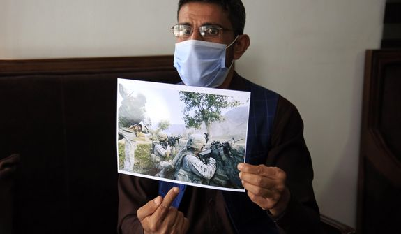 In this Friday, April 30, 2021, photo, Ayazudin Hilal, 40, a former Afghan interpreter for the U.S. shows his picture with U.S. Army soldiers during an interview to The Associated Press after a protest against the U.S. government and NATO in Kabul, Afghanistan. (AP Photo/Mariam Zuhaib)  ** FILE **