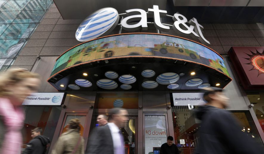 In this Oct. 21, 2014, file photo, people pass an AT&T store in New York's Times Square. AT&T will combine its media operations that include CNN HBO, TNT and TBS in a $43 billion deal with Discovery, the owner of lifestyle networks including the Food Network and HGTV. The deal announced Monday, May 17, 2021, would create a separate media company as households increasingly abandon cable and satellite TV, looking instead at Netflix, Amazon Prime Video, Facebook, TikTok and YouTube. (AP Photo/Richard Drew, File)