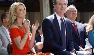 FILE-- In this July 1, 2019, file photo, First Partner Jennifer Siebel Newsom, left, attends a big signing ceremony with her husband, Gov. Gavin Newsom, right, at Sacramento City College in Sacramento, Calif. The Newsoms made about $500,000 more in 2019, Gavin Newsom's first year as governor, than they did before, according to tax returns released on May 17, 2021. Newsom, a Democrat, has pledged to release his returns every year. (AP Photo/Rich Pedroncelli, File)