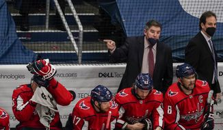 Washington Capitals Head Coach Peter Laviolette, second from right standing, speaks to the officials during the second period of Game 2 of an NHL hockey Stanley Cup first-round playoff series against the Boston Bruins, Monday, May 17, 2021, in Washington. (AP Photo/Alex Brandon) **FILE**