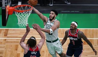 Boston Celtics forward Jayson Tatum drives to the basket against Washington Wizards center Robin Lopez (15) during the second half of an NBA basketball Eastern Conference play-in game Tuesday, May 18, 2021, in Boston. At right is Wizards guard Bradley Beal. (AP Photo/Charles Krupa)