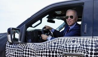 President Joe Biden stops to talk to the media as he drives a Ford F-150 Lightning truck at Ford Dearborn Development Center, Tuesday, May 18, 2021, in Dearborn, Mich. (AP Photo/Evan Vucci) ** FILE **