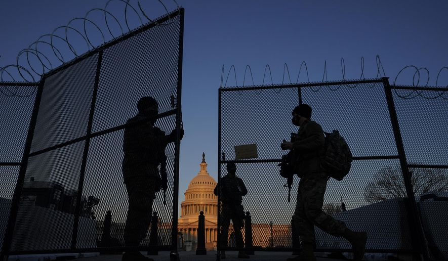 In this March 8, 2021, file photo, members of the National Guard open a gate in the razor wire topped perimeter fence around the Capitol at sunrise in Washington. Threats to members of Congress have more than doubled this year, according to the U.S. Capitol Police, and many members say they fear for their personal safety more than they did before the siege. (AP Photo/Carolyn Kaster, File)