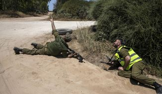 Israeli soldiers take cover on the ground as a siren sounds a warning of incoming rockets fired from the Gaza Strip, near the Israeli-Gaza border, in southern Israel, Monday, May 17, 2021. (AP Photo/Heidi Levine)