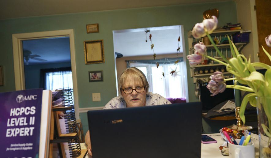 """Ellen Booth, 57, studies at her kitchen table to become a certified medical coder, in Coventry, R.I., Monday, May 17, 2021. When the restaurant she worked for closed last year, Booth said it gave her """"the kick I needed."""" She started a year-long class to learn to be a medical coder. When her unemployment benefits ran out two months ago, she started drawing on her retirement funds. Booth hopes to pass her upcoming exam and soon hit the job market. (AP Photo/David Goldman)"""