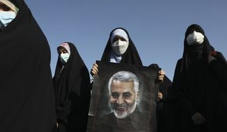 A demonstrator holds a poster of Iranian Revolutionary Guard Gen. Qassem Soleimani, who was killed in Iraq in a U.S. drone attack in early January 2020, in a pro-Palestinians gathering in Tehran, Iran, Wednesday, May 19, 2021. Chief of the powerful Revolutionary Guard Gen. Hossein Salami said in the gathering that Israel has become weaker and the Palestinians have become stronger and more powerful. Iran does not recognize Israel and supports anti-Israeli militant groups like Palestinian Hamas and Lebanon's Hezbollah. (AP Photo/Vahid Salemi)