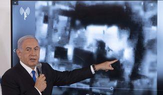 Israeli Prime Minister Benjamin Netanyahu gestures as he shows a slideshow during a briefing to ambassadors to Israel at the Hakirya military base in Tel Aviv, Israel, Wednesday, May 19, 2021. (AP Photo/Sebastian Scheiner, Pool)
