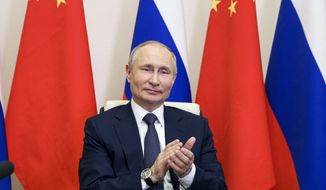 Russian President Vladimir Putin applauds as he takes part in a virtual unveiling of a nuclear power plant in China together with Chinese President Xi Jinping via video conference at the Novo-Ogaryovo residence outside Moscow, Russia, Wednesday, May 19, 2021. (Sergei Ilyin, Sputnik, Kremlin Pool Photo via AP)