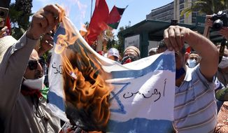 Supporters of the Palestinians burn an Israeli flag during a demonstration in Tunis, Wednesday, May 19, 2021. Despite growing international pressure for a cease-fire, the military said Wednesday it widened its strikes on militant targets in the Palestinian territory's south to blunt continuing rocket fire from Hamas. (AP Photo/Hassene Dridi)