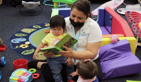 This May 4, 2021, file image shows teacher Graciela Olague-Barrios reading to two infants at Cuidando Los Ninos in Albuquerque, N.M. The charity provides housing, child care and financial counseling for mothers. (AP Photo/Susan Montoya Bryan) ** FILE **