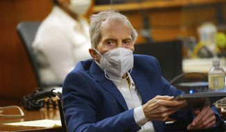 Robert Durst holds a device to read the real-time spoken script as he appears in the courtroom of Judge Mark E. Windham as attorneys begin opening statements in the trial of the real estate scion charged with murder of longtime friend Susan Berman, at Los Angeles County Superior Court, Tuesday, May 18, 2021, in Inglewood, Calif. Durst's murder trial was delayed more than a year due to the COVID-19 pandemic. (Al Seib/Los Angeles Times via AP, Pool)