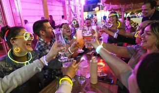 """Emily Baumgartner, left, and Luke Finley, second from left, join friends from their church group in a birthday toast to one of the members, upper right, during their weekly """"Monday Night Hang"""" gathering at the Tiki Bar on Manhattan's Upper West Side Monday, May 17, 2021, in New York. Under the latest regulations, vaccinated New Yorkers can shed their masks in most situations Wednesday. Restaurants, shops, gyms and many other businesses can go back to full occupancy if all patrons are inoculated. (AP Photo/Kathy Willens)"""